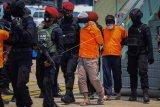 Personel Densus 88 Anti Teror membawa terduga teroris menuju mobil tahanan setibanya di Bandara Internasional Soekarno Hatta, Tangerang, Banten, Kamis (18/3/2021). Sebanyak 22 tahanan kasus terorisme jaringan Jamaah Islamiyah (JI) dari Jawa Timur tiba di Bandara Soekarno Hatta dan selanjutnya dibawa ke Rutan Cikeas, Bogor, Jawa Barat. ANTARA FOTO/Fauzan/wsj.