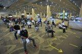 Sejumlah petugas bandara mengantre untuk menjalani vaksinasi COVID-19 di kawasan Terminal Internasional Bandara Internasional I Gusti Ngurah Rai, Badung, Bali, Senin (22/3/2021). Vaksinasi kepada 5.000 orang petugas dari berbagai instansi komunitas Bandara Ngurah Rai itu dilakukan untuk mencegah penyebaran pandemi COVID-19 sekaligus sebagai persiapan pembukaan penerbangan internasional di bandara tersebut yang rencananya dilakukan pada pertengahan tahun 2021 mendatang. ANTARA FOTO/Fikri Yusuf/nym.