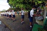 Siswa mencuci tangan saat akan memasuki area sekolah dalam pembelajaran tatap muka (PTM) di SMP Negeri Hindu 2 Sukawati, Gianyar, Bali, Selasa (23/3/2021). Pemerintah Kabupaten Gianyar membuka pembelajaran tatap muka bagi siswa SD dan SMP yang dimulai pada Selasa (23/3/2021) dengan menerapkan protokol kesehatan, mengatur jumlah siswa 20 orang setiap kelas serta membagi waktu belajar menjadi dua sesi, yakni sesi pertama pukul 07.30 WITA - 09.30 WITA dan sesi kedua 10.00 WITA - 12.00 WITA. ANTARA FOTO/Nyoman Hendra Wibowo/nym.