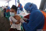 Petugas kesehatan menyuntikkan vaksin COVID-19 Astrazeneca kepada santri di pondok pesantren Lirboyo, Kota Kediri, Jawa Timur, Selasa (23/3/2021). Seluruh santri pondok pesantren Lirboyo ditargetkan mendapatkan suntikan vaksin Astrazeneca sebelum bulan ramadhan sebagai upaya menanggulangi penyebaran COVID-19 di lingkungan pesantren. Antara Jatim/Prasetia Fauzani/zk