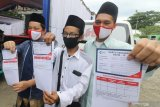 Tiga orang santri memperlihatkan kartu vaksin usai mendapatkan suntikan vaksin COVID-19 Astrazeneca di pondok pesantren Lirboyo, Kota Kediri, Jawa Timur, Selasa (23/3/2021). Seluruh santri pondok pesantren Lirboyo ditargetkan mendapatkan suntikan vaksin Astrazeneca sebelum bulan ramadhan sebagai upaya menanggulangi penyebaran COVID-19 di lingkungan pesantren. Antara Jatim/Prasetia Fauzani/zk