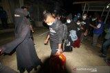 Pengungsi etnis Rohingya berjalan menuju bus saat akan diberangkatkan dari tempat penampungan Balai Latihan Kerja (BLK) Desa Meunasah Mee Kandang, Muara Dua, Lhokseumawe, Aceh, Kamis (25/2/2021) malam. Sebanyak 36 dari 92 sisa pengungsi Rohingya dipindahkan ke Medan, Sumatera Utara untuk mengikuti program penanganan pengungsi lintas negara oleh Internasional Organizational for Migration (IOM). ANTARA FOTO/Rahmad/wsj.