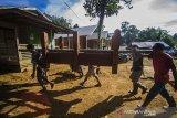 Sejumlah warga bergotong royong memikul rumah untuk di bawa ke makam saat tradisi membatur di Desa Ajung, Kabupaten Balangan, Kalimantan Selatan, Jumat (26/3/2021). Masyarakat Dayak Pitap menggelar tradisi membatur yang bertujuan untuk membuatkan rumah bagi orang yang telah meninggal dunia. Foto Antaranews Kalsel/Bayu Pratama S.ANTARA FOTO/BAYU PRATAMA S (ANTARA FOTO/BAYU PRATAMA S)