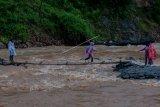 Warga melintasi sungai Ciberang menggunakan jembatan swadaya masyarakat di Desa Ciladaheun, Lebak, Banten, Selasa (30/3/2021). Menurut keterangan warga setempat, setahun pasca diterjang bencana banjir bandang jembatan yang merupakan akses jalan nasional tersebut belum dibangun dan tidak bisa dilalui kendaraan ketika hujan deras karena air sungai Ciberang meluap. ANTARA FOTO/Muhammad Bagus Khoirunas/aww.