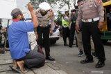 Petugas memeriksa warga yang melintas di jalan Raya Waru, Perbatasan Surabaya - Sidoarjo, Jawa Timur, Kamis (1/4/2021). Pemeriksaan dan penyekatan di titik perbatasan tersebut sebagai upaya meningkatkan pengamanan dan mengantisipasi ancaman teror. Antara Jatim/Umarul Faruq/zk.