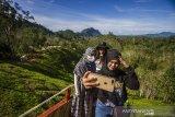 Sejumlah pengunjung berswafoto di puncak wisata kampung bambu, Desa Tandilang, Kabupaten Hulu Sungai Tengah, Kalimantan Selatan, Minggu (4/4/2021).  Wisata alam yang di kelola oleh warga setempat tersebut menawarkan pemandangan Pegunungan Meratus serta menyediakan tempat berfoto dan camping ground untuk menjadi daya tarik wisatawan. Foto Antaranews Kalsel/Bayu Pratama S.ANTARA FOTO/BAYU PRATAMA S (ANTARA FOTO/BAYU PRATAMA S)