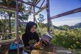 Seorang pengunjung bersantai di puncak wisata kampung bambu, Desa Tandilang, Kabupaten Hulu Sungai Tengah, Kalimantan Selatan, Minggu (4/4/2021). Wisata alam yang di kelola oleh warga setempat tersebut menawarkan pemandangan Pegunungan Meratus serta menyediakan tempat berfoto dan camping ground untuk menjadi daya tarik wisatawan. Foto Antaranews Kalsel/Bayu Pratama S.ANTARA FOTO/BAYU PRATAMA S (ANTARA FOTO/BAYU PRATAMA S)