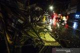 Sejumlah warga berada di dekat dinding bangunan yang ambruk di kawasan Pasar Ujung Murung di Jalan Sudimampir, Banjarmasin, Kalimantan Selatan, Senin (5/4/2021). Dinding di lantai tiga bangunan Pasar Ujung Murung ambruk mengakibatkan satu unit sepeda motor tertimpa reruntuhan bangunan. Foto Antaranews Kalsel/Bayu Pratama S.