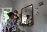 Pemuda Karang Taruna Jantikidul memberikan layanan jasa perawatan rambut kepada seorang pelanggan di bangunan bekas balai RW yang diubah menjadi kios pangkas rambut atau barbershop di Malang, Jawa Timur, Senin (5/4/2021). Usaha pangkas rambut tersebut didirikan Karang Taruna setempat untuk menampung serta memberdayakan kembali pemuda pekerja yang terkena PHK akibat pandemi COVID-19 sekaligus menambah Pendapatan Asli Desa (PADes) melalui unit usaha dengan sistem bagi hasil. Antara Jatim/Ari Bowo Sucipto./zk