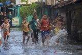 Anak-anak bermain air saat banjir akibat luapan Sungai Martapura di Kelayan A, Banjarmasin, Kalimantan Selatan, Senin (5/4/2021). Hujan deras yang mengguyur sejumlah wilayah di Provinsi Kalimantan Selatan beberapa hari belakangan ini membuat kanal dan Sungai Martapura di Kota Banjarmasin meluap sehingga mengakibatkan sejumlah rumah dan jalan terendam banjir. Foto Antaranews Kalsel/Bayu Pratama S.