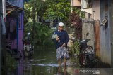Seorang warga melintasi banjir akibat luapan sungai Martapura di Kelayan A, Banjarmasin, Kalimantan Selatan, Senin (5/4/2021). Hujan deras yang mengguyur sejumlah wilayah di Provinsi Kalimantan Selatan beberapa hari belakangan ini membuat kanal dan Sungai Martapura di Kota Banjarmasin meluap sehingga mengakibatkan sejumlah rumah dan jalan terendam banjir. Foto Antaranews Kalsel/Bayu Pratama S.