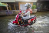 Pengendara motor melintasi banjir akibat luapan Sungai Martapura di Kelayan A, Banjarmasin, Kalimantan Selatan, Senin (5/4/2021). Hujan deras yang mengguyur sejumlah wilayah di Provinsi Kalimantan Selatan beberapa hari belakangan ini membuat kanal dan Sungai Martapura di Kota Banjarmasin meluap sehingga mengakibatkan sejumlah rumah dan jalan terendam banjir. Foto Antaranews Kalsel/Bayu Pratama S.