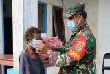 Babinsa Koramil Tanah Merah bagi masker dan baju kaos ke warga Kawagit