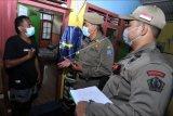 Petugas melakukan pemeriksaan identitas penduduk saat razia kependudukan di kawasan Legian, Kuta, Badung, Bali, Selasa (6/4/2021). Razia tersebut dilakukan untuk menertibkan administrasi kependudukan penduduk non permanen serta mengantisipasi masuknya anggota jaringan teroris ke wilayah Bali. ANTARA FOTO/Fikri Yusuf/nym.