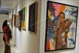Pengunjung mengamati karya seni rupa yang dipajang dalam pameran bertajuk