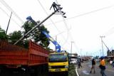 Sejumlah pekerja memperbaiki tiang listrik yang ambruk akibat angin kencang di pinggir jalan trans di Desa Belang-belang, Mamuju, Sulawesi Barat, Selasa (6/4/2021). Sejak tiga hari terakhir, Sulbar dan sekitarnya dilanda cuaca buruk angin kencang disertai hujan dengan ketinngian gelombang laut mencapai dua meter lebih . ANTARA FOTO / Akbar Tado/foc.