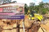 Petugas mengoperasikan alat berat untuk menutup sumur minyak ilegal yang ditinggalkan pemiliknya saat penertiban di Taman Hutan Raya Sultan Thaha Syaifuddin, Batanghari, Jambi, Senin (5/4/2021). Puluhan personel gabungan dari Polda Jambi, Polres Batanghari dan instansi terkait menutup puluhan sumur minyak ilegal melalui operasi