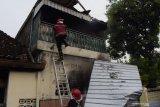 Petugas memadamkan api saat terjadi kebakaran rumah warga di Kota Madiun, Jawa Timur, Rabu (7/4/2021). Menurut warga, rumah tersebut terbakar akibat kompor gas elpiji dan menyebabkan pemilik rumah mengalami luka bakar. Antara Jatim/Siswowidodo/zk