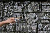 Pekerja membersihkan lumut yang tumbuh di relief candi Jago dengan menggunakan lidi di Tumpang, Malang, Jawa Timur, Kamis (8/4/2021). Pembersihan lumut tersebut dilakukan secara rutin untuk mencegah kerusakan pada relief dan batuan candi Buddha yang dibangun pada tahun 1268 Masehi oleh Raja Kertanegara. Antara Jatim/Ari Bowo Sucipto/zk