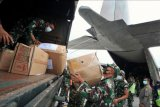 Prajurit TNI memindahkan bantuan logistik dari truk ke pesawat Hercules C-130 di Lanud I Gusti Ngurah Rai, Bali, Jumat (9/4/2021). Berbagai bantuan logistik seperti bahan makanan, pakaian layak pakai dan kebutuhan bayi seberat lima ton tersebut diangkut menuju Kupang untuk membantu korban bencana alam badai siklon tropis Seroja di wilayah Nusa Tenggara Timur (NTT). ANTARA FOTO/Fikri Yusuf/nym.