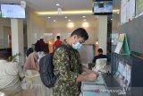 PENERAPAN QANUN LEMBAGA KEUANGAN SYARIAH DI ACEH. Seorang nasabah mengisi slip setoran saat melakukan transaksi keuangan di kantor cabang BNI Syariah Indonesia, Banda Aceh, Aceh, Kamis (8/4/2021). Penerapan Qanun (peraturan daerah) nomor 11 tahun 2018  tentang Lembaga Keuangan Syariah di Aceh mewajibkan semua perbankan di daerah itu memiliki Unit Syariah dan terhitung pada Juni 2021 beberapa bank konvensional yang tidak memiliki Unit Syariah tersebut, dilaporkan akan tutup  beroperasi di Aceh. ANTARA FOTO/Ampelsa.