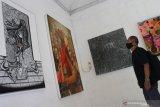 Pengunjung mengamati lukisan yang dipajang dalam pameran seni rupa bertajuk N-Battleground di gedung Dewan Kesenian Malang, Jawa Timur, Jumat (9/4/2021). Pameran yang berlangsung selama lima hari tersebut menampilkan puluhan karya berupa lukisan, instalasi dan patung dari 46 seniman dengan mengangkat tema tragedi kehidupan dan kritik sosial. Antara Jatim/Ari Bowo Sucipto/zk