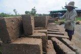 Perajin menjemur batu bata di Desa Mortajih, Pamekasan, Jawa Timur, Sabtu (10/4/2021). Menurut perajin,  produksi batu bata di daerah itu terkendala proses pengeringan yang mencapai hingga mencapai satu minggu dari biasanya  kering dalam dua hari karena masih tingginya curah hujan. Antara Jatim/Saiful Bahri/zk
