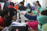 Petugas memeriksa kondisi kesehatan karyawan sebelum menyuntikkan vaksin COVID-19 di salah satu pusat perbelanjaan di Kota Kediri, Jawa Timur, Sabtu (10/4/2021). Dinas kesehatan daerah setempat menyuntikkan vaksin secara serentak kepada karyawan pasar modern se-Kota Kediri guna memutus mata rantai penyebaran COVID-19. Antara Jatim/Prasetia Fauzani/zk