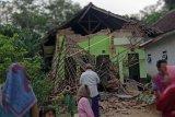 Warga menyaksikan rumah yang rusak akibat gempa di Kecamatan Turen, Kabupaten Malang, Jawa Timur, Sabtu (10/4/2021). Gempa berkekuatan kurang lebih magnitudo (m) 6,7 yang terjadi di wilayah Kabupaten Malang tersebut menyebabkan sejumlah rumah warga rusak dan guncangan di sejumlah wilayah di Jawa Timur. ANTARA FOTO/STR/SA/nym.
