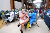 Vaksinator menyuntikkan vaksin COVID-19 kepada seorang warga negara asing yang menetap di Bali saat pelaksanaan vaksinasi di Discovery Shopping Mall, Kuta, Badung, Bali, Sabtu (10/4/2021). Pemkab Badung bekerja sama dengan pengelola pusat perbelanjaan tersebut menyediakan lokasi vaksinasi COVID-19 di mal yang mampu melayani hingga 900 orang per hari sebagai salah satu upaya untuk mempercepat pelaksanaan vaksinasi bagi masyarakat guna menekan laju penyebaran COVID-19 serta memulihkan sektor ekonomi dan pariwisata di kawasan Kuta. ANTARA FOTO/Fikri Yusuf/nym.