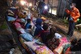 Bupati Lumajang Thoriqul Haq (kanan) berbincang dengan warga yang mengungsi ketika meninjau lokasi terdampak gempa di Desa Kali Uling, Lumajang, Jawa Timur, Minggu (11/4/2021). Sekitar ratusan rumah warga di wilayah itu rusak akibat gempa yang terjadi di Kabupaten Malang .  Antara Jatim/Zabur Karuru