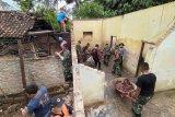 Sejumlah anggota TNI/Polri bersama relawan bergotong royong mengevakuasi perabot dari dalam rumah warga yang ambruk terdampak gempa di Trenggalek, Jawa Timur, Ahad (11/4/2021). Di daerah ini, tercatat ada 63 bangunan yang tersebar di 27 desa 11 kecamatan dilaporkan rusak terdampak gempa bermagnitudo 6,7 dengan episentrum sekitar 90 kilometer arah barat daya Kabupaten Malang dan kedalaman sekitar35 kilometer bawah laut Samudera Indonesia pada Sabtu (10/4) siang. Antara Jatim/Destyan Sujarwoko/zk.