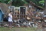 Seorang ibu menelepon di depan rumahnya yang hancur akibat gempa di Majangtengah, Malang, Jawa Timur, Minggu (11/4/2021). Badan Nasional Penanggulangan Bencana (BNPB) melaporkan sedikitnya 1.189 unit rumah rusak akibat gempa bermagnitudo 6,1 yang mengguncang kawasan Malang dan sekitarnya. Antara Jatim/Ari Bowo Sucipto/zk.