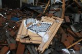 Sebuah hiasan rumah berupa kaligrafi berada diantara puing reruntuhan sebuah rumah yang rusak akibat gempa di Majangtengah, Malang, Jawa Timur, Minggu (11/4/2021). Badan Nasional Penanggulangan Bencana (BNPB) melaporkan sedikitnya 1.189 unit rumah rusak akibat gempa bermagnitudo 6,1 yang mengguncang kawasan Malang dan sekitarnya. Antara Jatim/Ari Bowo Sucipto/zk.