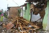 Seorang ibu berdiri di depan rumahnya yang hancur akibat gempa di Majangtengah, Malang, Jawa Timur, Minggu (11/4/2021). Badan Nasional Penanggulangan Bencana (BNPB) melaporkan sedikitnya 1.189 unit rumah rusak akibat gempa bermagnitudo 6,1 yang mengguncang kawasan Malang dan sekitarnya. Antara Jatim/Ari Bowo Sucipto/zk.