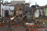 Seorang warga melintas di depan rumah yang rusak akibat gempa di Majangtengah, Malang, Jawa Timur, Minggu (11/4/2021). Badan Nasional Penanggulangan Bencana (BNPB) melaporkan sedikitnya 1.189 unit rumah rusak akibat gempa bermagnitudo 6,1 yang mengguncang kawasan Malang dan sekitarnya. Antara Jatim/Ari Bowo Sucipto/zk.