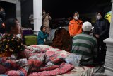 Menteri Sosial Tri Rismaharini (kanan) bersama Bupati Lumajang Thoriqul Haq (ketiga kanan) berbincang dengan warga terdampak gempa yang beristirahat di teras rumahnya di Desa Kali Uling, Lumajang, Jawa Timur, Minggu (11/4/2021). Dalam kunjungannya, Mensos Tri Rismaharini memberikan bantuan kepada warga yang terdampak gempa dan meminta pemerintah setempat  segera mencari lokasi yang aman untuk dibangun posko pengungsian.  Antara Jatim/Zabur Karuru