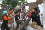 Relawan membantu warga menyelamatkan barang-barang di sebuah rumah yang hancur akibat gempa di Majangtengah, Malang, Jawa Timur, Minggu (11/4/2021). Kementerian Sosial menerjunkan 700 personel Tagana di sejumlah lokasi terdampak bencana gempa Malang untuk membantu mengevakuasi korban, membangun tempat pengungsian, mendirikan dapur umum dan  menyelenggarakan layanan dukungan psikososial. Antara Jatim/Ari Bowo Sucipto/zk.