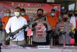 Kabid Humas Polda Jawa Timur  Kombes Pol Gatot Repli Handoko (tengah) bersama Kapolresta Banyuwangi Kombes Pol Arman Asmara Syarifuddin (kanan) menunjukan tersangka beserta barang bukti dalam rilis kasus senjata api ilegal di Polresta Banyuwangi, Jawa Timur, Sabtu (10/4/2021). Polisi menangkap empat tersangka serta mengamankan 36 barang bukti diantaranya senjata laras panjang jenis M16, amunisi, mesin bubut dan serbuk misiu. Antara Jatim/Budi Candra Setya/zk.