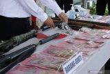 Polisi menata barang bukti dalam rilis kasus senjata api ilegal di Polresta Banyuwangi, Jawa Timur, Sabtu (10/4/2021). Polisi menangkap empat tersangka serta mengamankan 36 barang bukti diantaranya senjata laras panjang jenis M16, amunisi, mesin bubut dan serbuk misiu. Antara Jatim/Budi Candra Setya/zk.