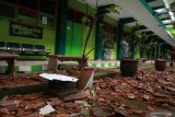 Seorang warga melintas di depan bangunan sekolah yang rusak akibat gempa di SMK Negeri 1 Turen, Malang, Jawa Timur, Sabtu (10/4/2021). Gempa dengan kekuatan 6,7 SR yang mengguncang kawasan Malang dan sekitarnya membuat sejumlah bangunan rusak. Antara Jatim/Bayu/abs/zk.