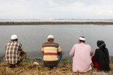 Warga korban lumpur memanjatkan doa untuk keluarga mereka yang telah wafat saat ziarah jelang ramadhan di tanggul Porong, Sidoarjo, Jawa Timur, Minggu (11/4/2021). Mereka berdoa dari pinggir tanggul karena makam keluarganya telah tenggelam oleh lumpur. Antara Jatim/Umarul Faruq/zk.