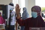 UJIAN TULIS BERBASIS KOMPUTER SBMPTN. Peserta didampingi petugas keamanan mengikuti pemeriksaan suhu badan sebelum mengikuti Ujian Tulis Berbasis Komputer (UTBK) jalur Seleksi Bersama Masuk Perguruan Tinggi Nasional (SBMPTN) di Universitas Syiah Kuala, Banda Aceh, Aceh, Senin (12/4/2021). Ujian Tulis Berbasis Komputer jalur SBMPTN yang diikuti sekitar 8.900 peserta berlangsung tanggal 12 hingga 16 April itu digelar dengan penerapan protokol kesehatan secara ketat guna mencegah penyebaran COVID-19. ANTARA FOTO/Ampelsa.