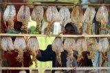 Seorang pedagang memilih sotong atau cumi kering untuk diolah saat Festival Kampong Sotong Pangkong (Sopang) di Jalan Merdeka Barat, Pontianak, Kalimantan Barat, Minggu (11/4/2021). Kampong Sopang yang difasilitasi Pemerintah Kota Pontianak tersebut menjadi wadah bagi para pelaku usaha kuliner untuk berjualan sopang atau cumi kering yang dibakar dan dipipihkan dengan menggunakan palu, kemudian disantap dengan cocolan sambal. ANTARA FOTO/Jessica Helena Wuysang