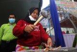 Pedagang Sotong Pangkong yaitu Mak Ida (kanan) menumbuk sotong atau cumi kering untuk dibakar dan dihidangkan saat Festival Kampong Sotong Pangkong (Sopang) di Jalan Merdeka Barat, Pontianak, Kalimantan Barat, Minggu (11/4/2021). Pedagang Sotong Pangkong yaitu Mak Ida memperlihatkan dua sotong atau cumi kering dan palu yang digunakan untuk mengolah saat Festival Kampong Sotong Pangkong (Sopang) di Jalan Merdeka Barat, Pontianak, Kalimantan Barat, Minggu (11/4/2021). Kampong Sopang yang difasilitasi Pemerintah Kota Pontianak tersebut menjadi wadah bagi para pelaku usaha kuliner untuk berjualan sopang atau cumi kering yang dibakar dan dipipihkan dengan menggunakan palu, kemudian disantap dengan cocolan sambal. ANTARA FOTO/Jessica Helena Wuysang