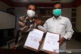 Kepala LKBN Antara Biro Kalbar Teguh Imam Wibowo (kanan) bersama Direktur Politeknik Negeri Sambas (Poltesa) Mahyus (kiri) memperlihatkan MoU atau nota kesepahaman yang telah ditandatangani di Kampus Poltesa di Kabupaten Sambas, Kalimantan Barat, Rabu (7/4/2021). LKBN Antara Biro Kalbar bersinergi dengan Poltesa yang merupakan satu-satunya perguruan tinggi di kawasan perbatasan Indonesia-Malaysia tersebut untuk publikasi hasil penelitian dan pengembangan potensi daerah perbatasan. ANTARA KALBAR/Jessica Helena Wuysang
