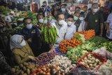 Menteri Perdagangan Muhammad Lutfi (tengah) bersama Gubernur Jawa Barat Ridwan Kamil (kedua kiri) berbincang dengan pedagang sayur saat melakukan kunjungan kerja di Pasar Kosambi, Bandung, Jawa Barat, Selasa (13/4/2021). Dalam kunjungan kerjanya di Bandung, Menteri Perdagangan berkesempatan memantau harga kebutuhan pokok pada hari pertama puasa di Pasar Kosambi dan Pasar Sederhana. ANTARA JABAR/Raisan Al Farisi/agr