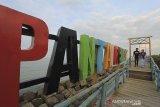 Sejumlah warga bersantai menunggu waktu berbuka puasa (ngabuburit) di Pantai Rembat, Juntinyuat, Indramayu, Jawa Barat, Selasa (13/4/2021). Pantai Rembat yang berada di Pantai Utara Jawa itu menjadi salah satu lokasi favorit warga saat bulan Ramadhan untuk menunggu waktu berbuka puasa sambil menikmati terbenamnya matahari. ANTARA JABAR/Dedhez Anggara/agr
