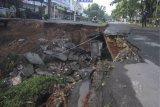 Warga memfoto jalan yang longsor di Jalan Raya Boulevard, GDC, Depok, Jawa Barat, Selasa (13/4/2021).Longsor yang terjadi pada Senin (12/4) pukul 21.00 WIB tersebut akibat intensitas hujan yang tinggi dan menyebabkan sebagain jalan amblas dengan kedalaman dan lebar kurang lebih 5 meter. ANTARA FOTO/Asprilla Dwi Adha/hp.