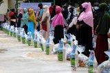 Warga antre mengambil paket sembako dari masyarakat muslim Eropa dan Turki di komplek SMA Modal Bangsa, Aceh Besar, Aceh, Rabu (14/4/2021). Masyarakat muslim Eropa dan Turki yang difasilitisi Yayasan Kafalah Indonesia dan alumni SMA Modal Bangsa menyalurkan 2.222 paket sembako untuk warga kurang mampu guna memenuhi kebutuhan Ramadhan. Antara Aceh/Irwansyah Putra.